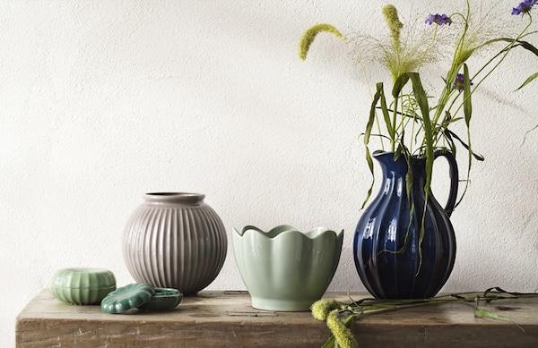 På en rustik bænk står 3 forskellige vaser i forskellige douche farver i  mørkeblå, lysegrøn og rosa. I den store blå vase står en buket kornblomster
