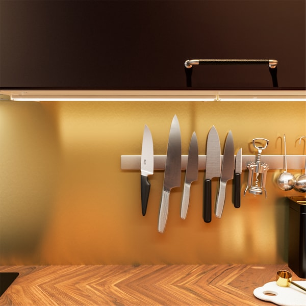 A kitchen worktop in walnut, a gold-colored wall panel, worktop lighting and a magnetic knife rack with knives.