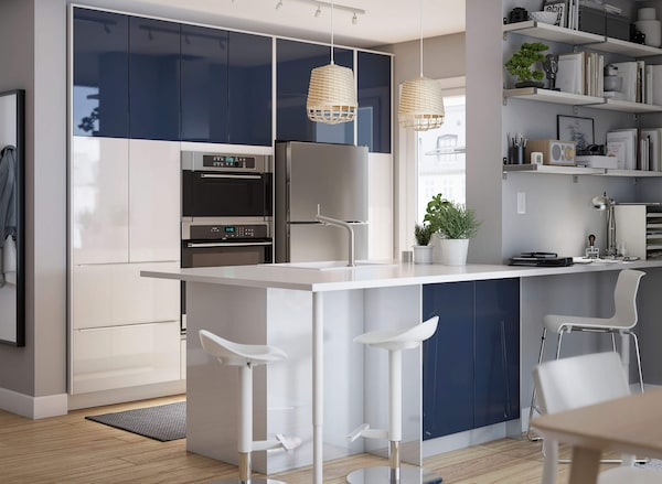 A high gloss white kitchen with dark blue accent doors and white bar stools under a bar countertop.