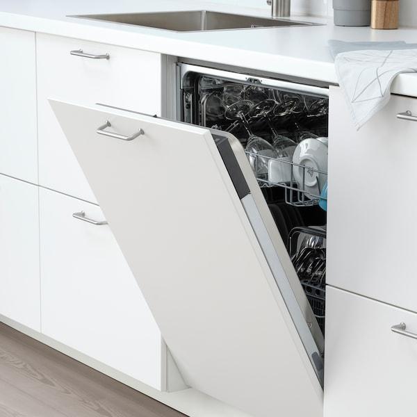 Cocina moderna de color blanco con lavavajillas integrado de IKEA abierto con platos y copas limpios.