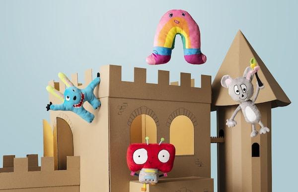 Un castello di cartone beige fa da sfondo a sei peluche colorati della serie SAGOSKATT di IKEA, basati sui disegni dei bambini dei soci IKEA Family.