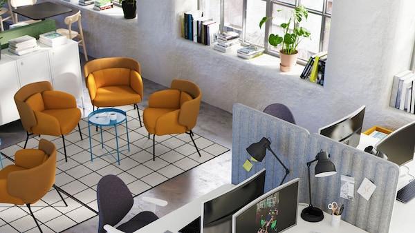 Egy helyiség pihenő részekkel, székekkel és dohányzóasztallal, és egy másik területtel, ahol íróasztalok, képernyők, székek és tárolóelemek vannak.