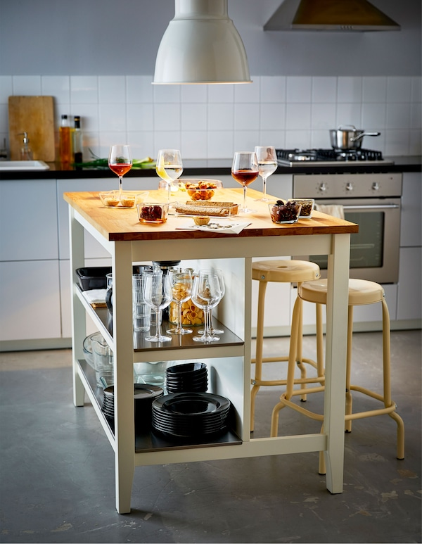 A large kitchen island holding snacks and glasses of wine, stores tableware on the shelves below.