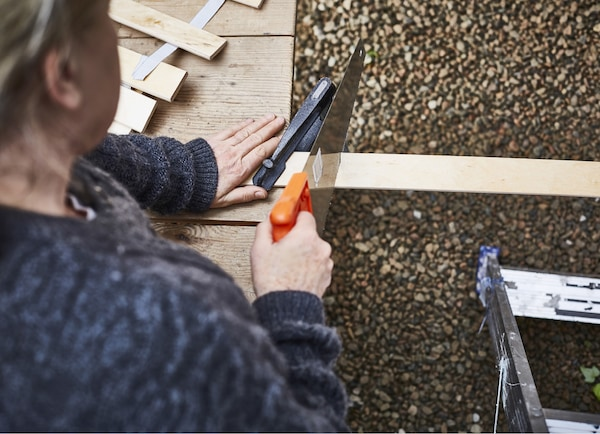 A woman sawing a piece of wood.