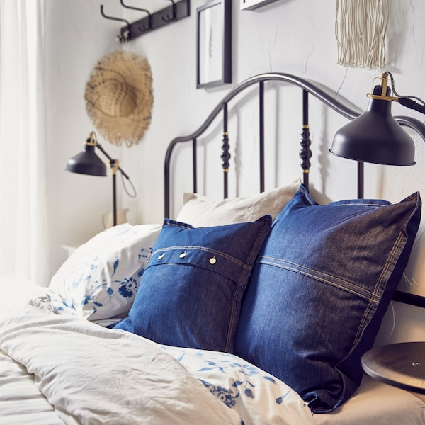 A bed with two IKEA SISSIL blue denim cushion covers amongst other pillows.
