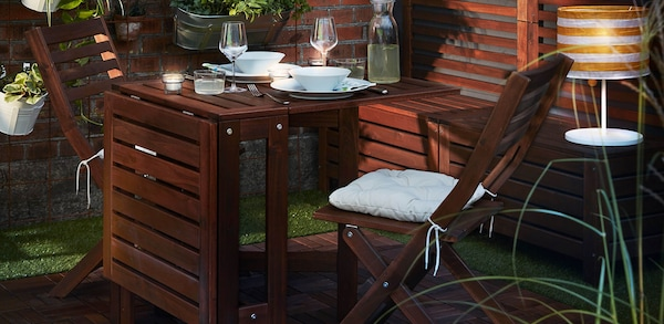Dark wood outdoor table with white dinnerware and wine glasses with matching chairs