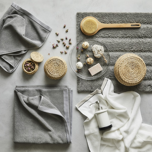 Grey towels and bathroom accessories laid out on a grey surface.