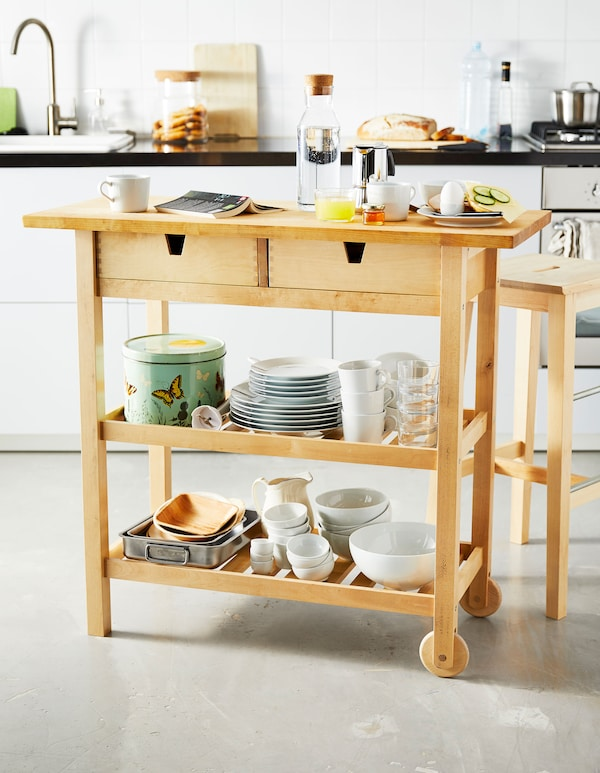 A small wooden kitchen island is set with breakfast foods and stores tableware on the shelves below.