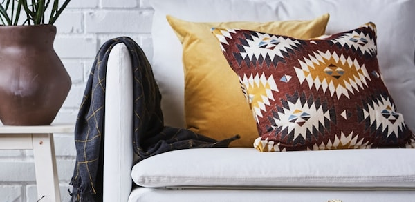Printed pillow with a yellow pillow on a white couch and plaid throw