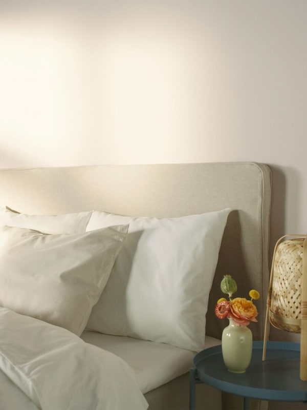 The top of a bed with headboard, dressed with bedding and pillows with a blue side table with a lamp and flowers.