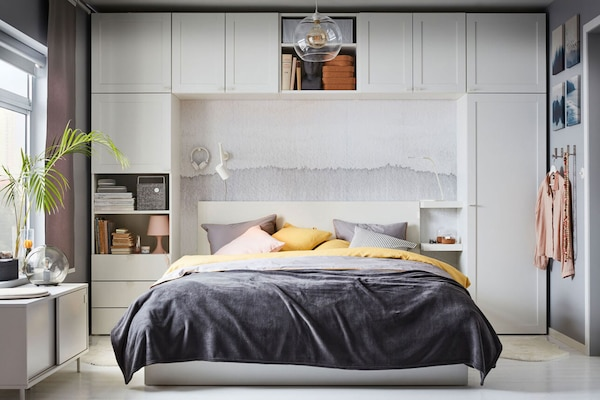 A bed with cushions and decorative throw surrounded by PLATSA storage.