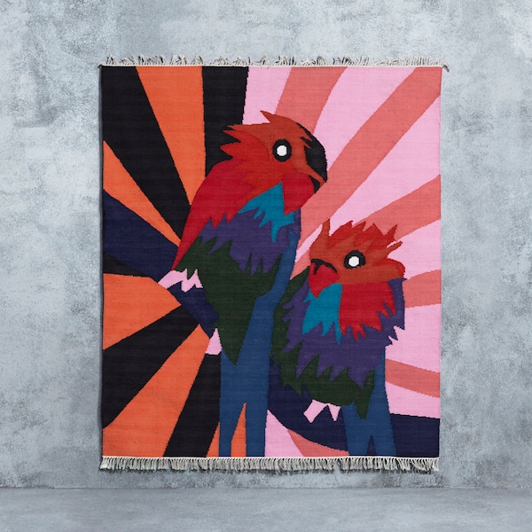 A handwoven rug in pink, red, blue and black featuring two big parrots, designed by Craig Green for IKEA ART EVENT 2019.
