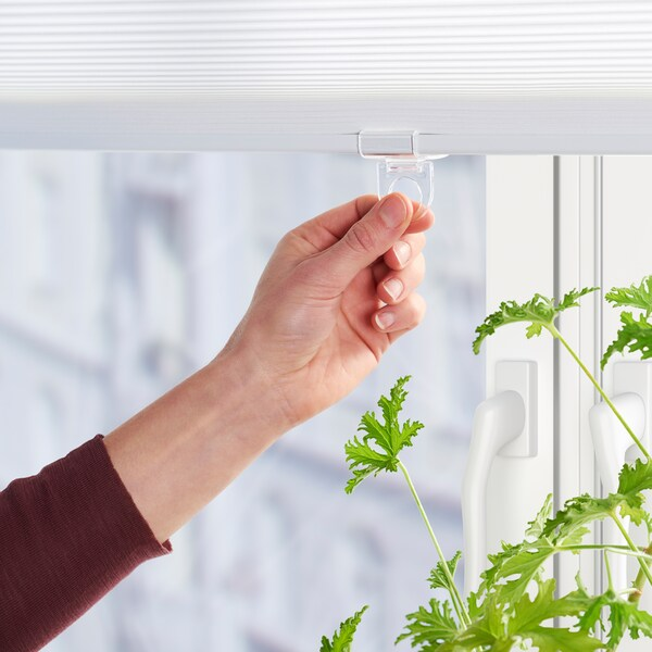 A hand holding the transparent plastic handle of a white cordless blind in a window with a green plant.