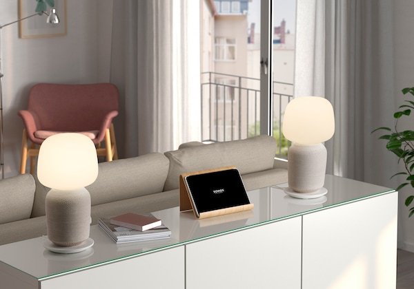 Two white SYMFONISK Table lamps with WiFi speakers sitting on a white sideboard cupboard behind a beige sofa