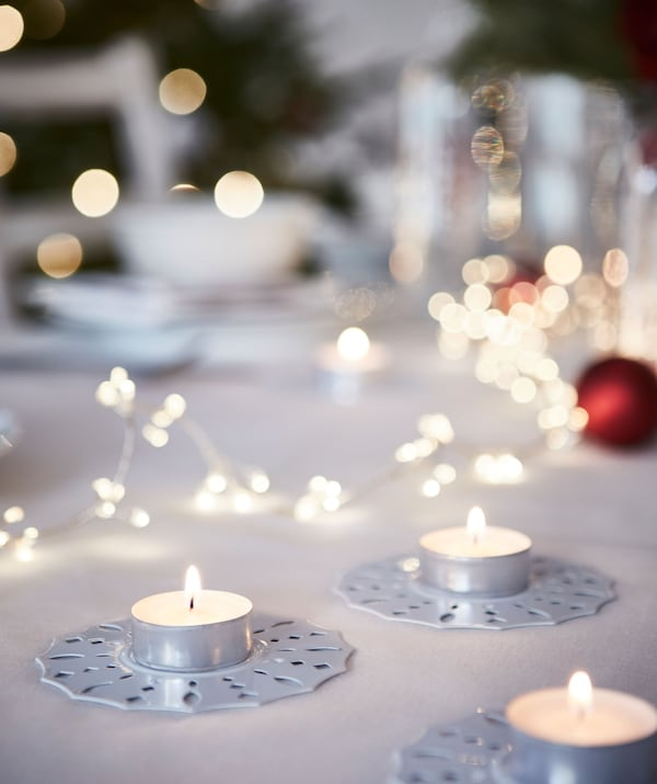 Eine Weihnachtstafel mit GLIMMA Teelichtern in dekorativen Haltern
