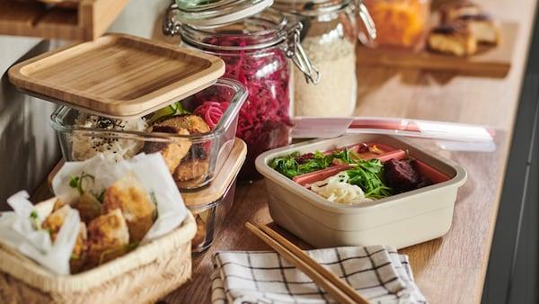 365+ voedselbakjes met eten erin op een houten werkblad.