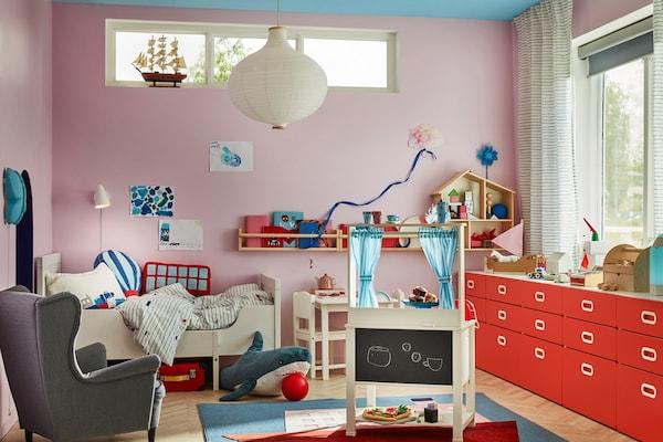 Kinderzimmer mit langer, roter Kommode, grauen Sessel, weißeren Kinderbett sowie weiteren Accessoires.
