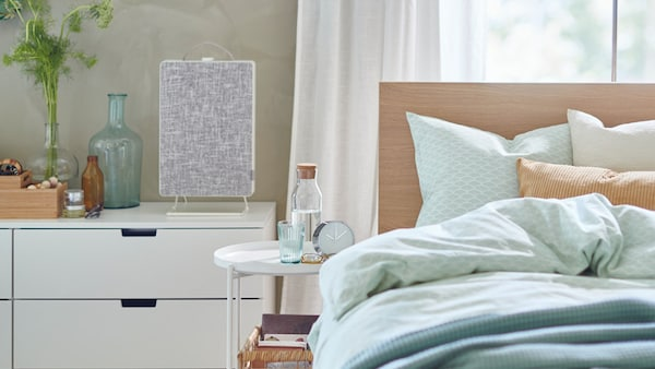 A bedroom with a MALM bed and a NORDLI dresser with the FORNUFTIG air purifier sitting on top.