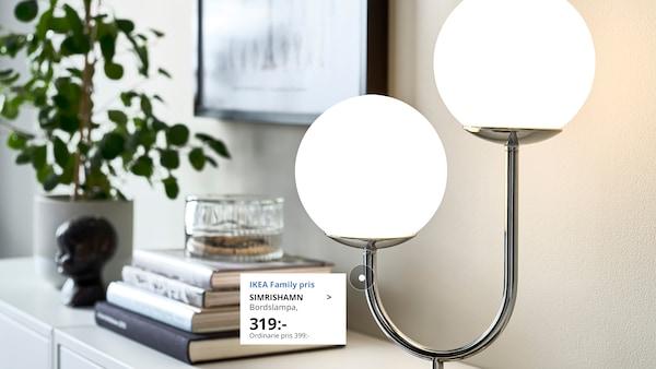 SIMRISHAMN bordslampa står på en byrå bredvid en hög med böcker, en kruka med växt i och dekoration.