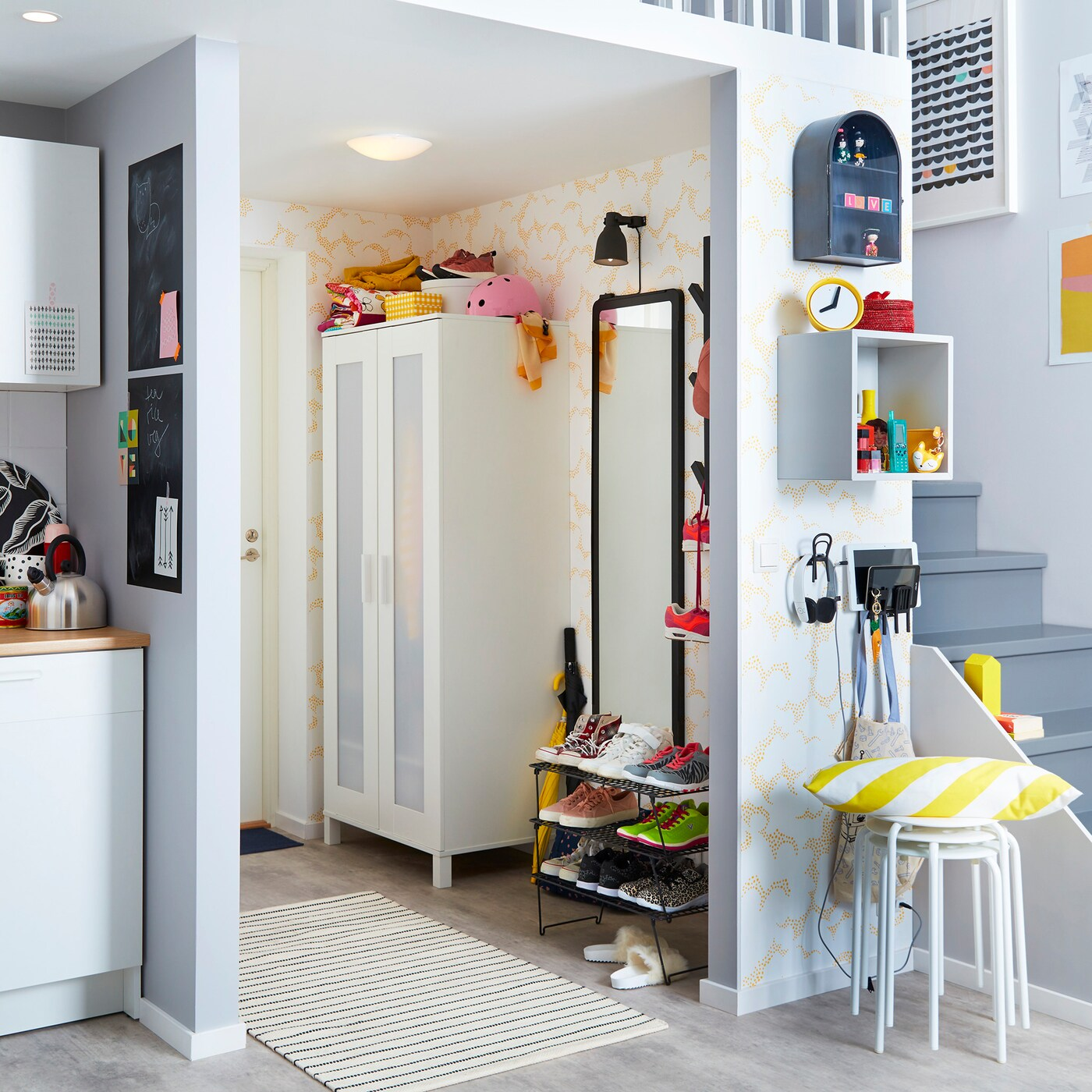 A hallway with ANEBODA wardrobe, a GREJIG shoe rack, a mirror and a white carpet on the floor and stairs in the background.