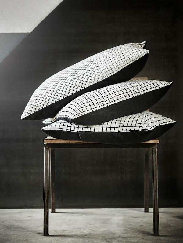 Three HANTVERK cushions, handmade in Jordan, in a pile on a small table.