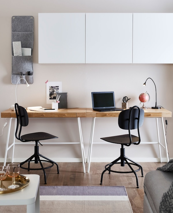 Two desks with light wood worktops in a living room area, sitting against a wall and beneath white wall cabinets.