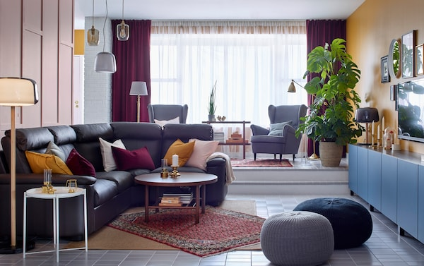 A dark brown corner leather sofa in a living room with storage, a very large window and two armchairs.