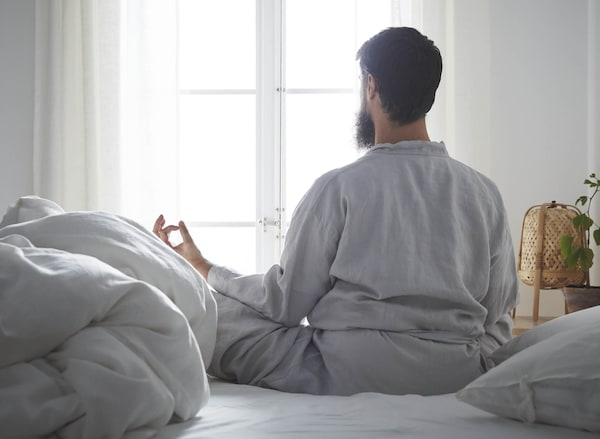 Man meditating in bed