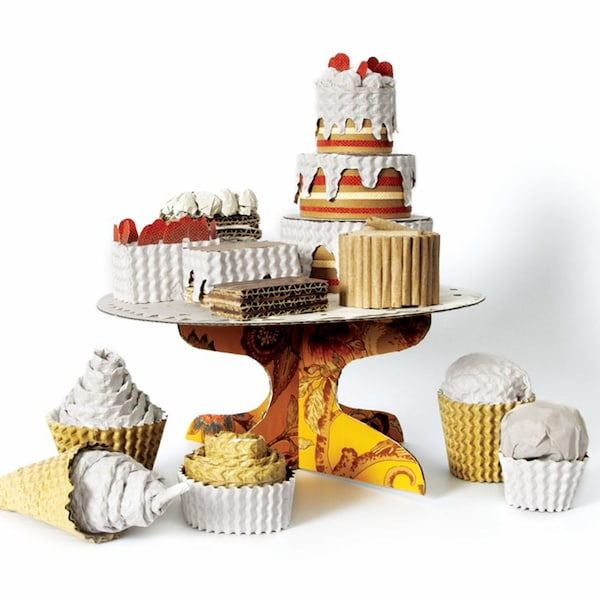 A platter of cakes, ice cream and other sweets made out of recycled packaging materials such as cardboard boxes.