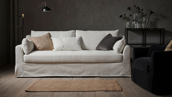 A white velvet sofa in a room with moody decor.