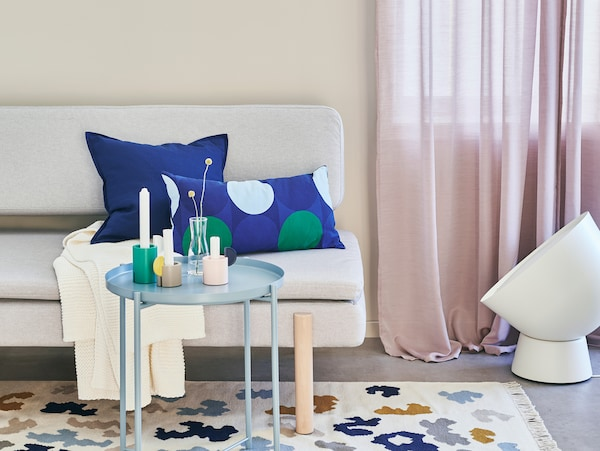 Room with table and sofa with colouful pillows.
