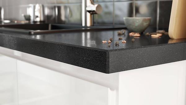 Black custom quartz countertop in a kitchen with white cabinets