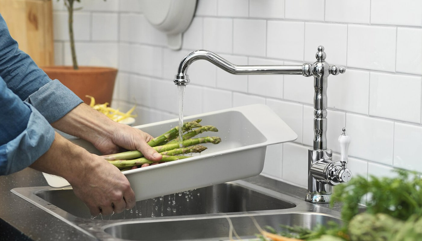 Hands washing vegetables under a running faucet and sink