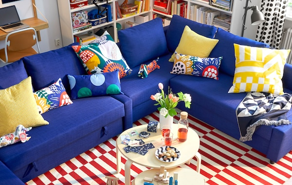 A blue corner sofa with colorful cushions, two round coffee tables and a striped rug.