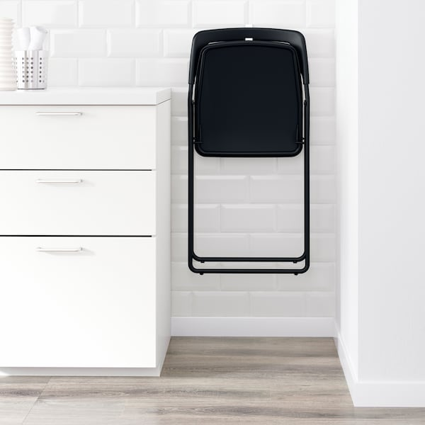 A black IKEA NISSE folding chair hanging on a white wall in a narrow space between a wall and a cabinet