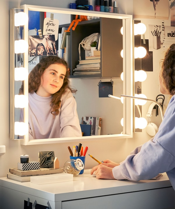 A girl looking into a mirror with lights above a white desk.