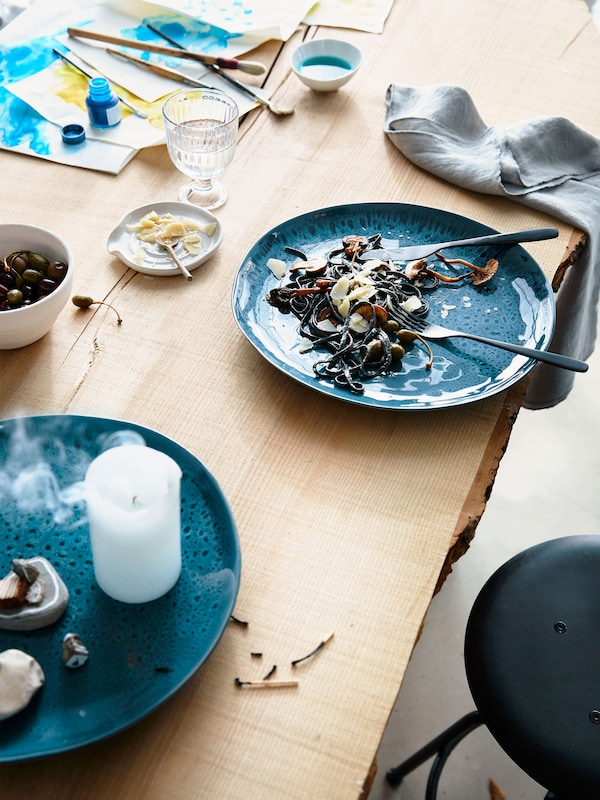 Pohled shora na modré kameninové talíře ERTAPPAD na stole