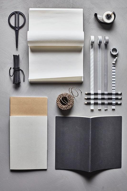Набор канцелярских товаров: черная книжка для записей, бежевая тесьма в черную полоску, скотч с черным диспенсером и скотчи с декоративным серым узором
