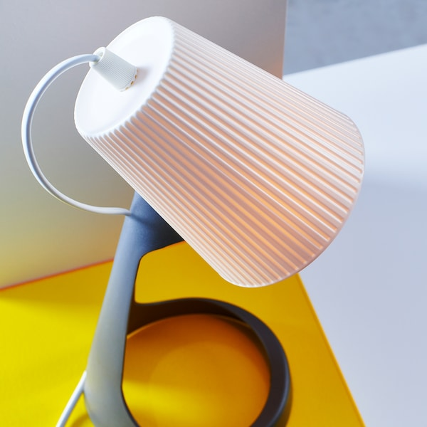 Close-up of SVALLET work lamp showing its targeted lamp shade in white and lamp base in dark grey.