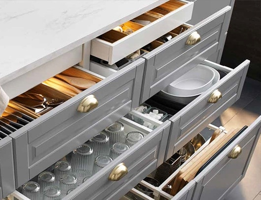 A kitchen cabinet section with open drawers showing glassware, plates and utensils.