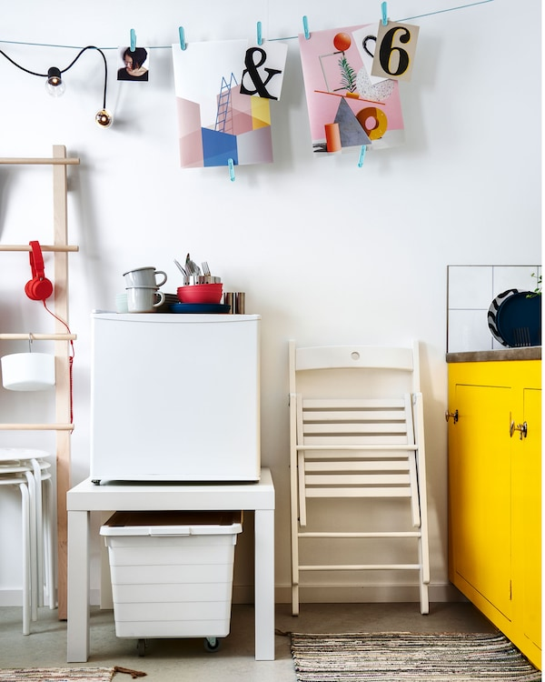 The area next to a kitchenette with wall decoration hung on a line. A small fridge stands on a LACK table, bin underneath.
