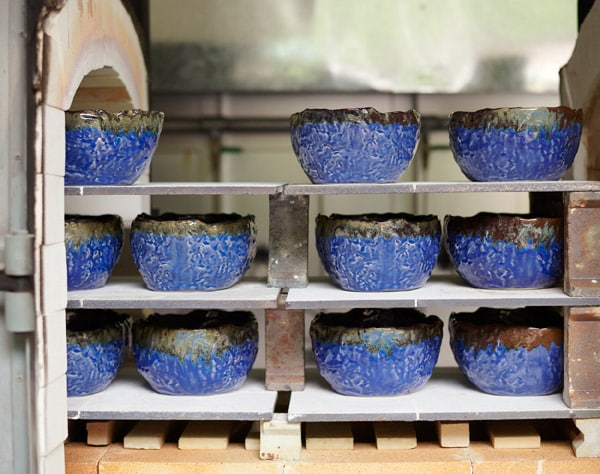 Handmade ceramic bowls with irregular shapes in dark blue and green created for the ANNANSTANS collection.
