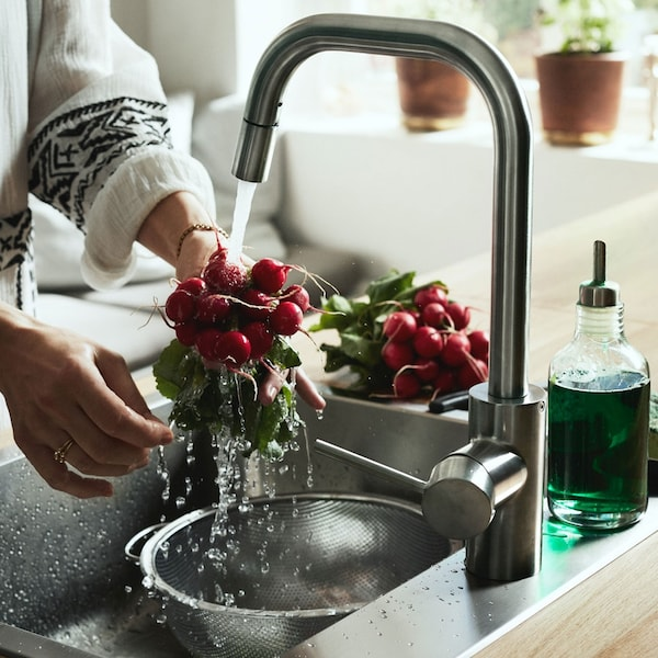 Woman washing radishes in sink using ÄLMAREN kitchen faucet with pull-out spout in stainless steel colour.