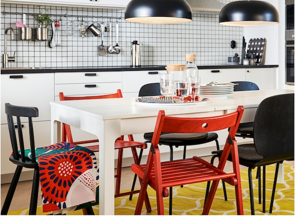 A kitchen with an extended table in white, red and black chairs, a yellow/white rug and two black pendant lamps.