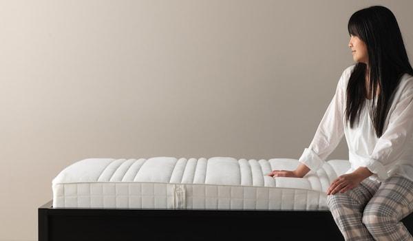 Девушка сидит на матрасе в спальне