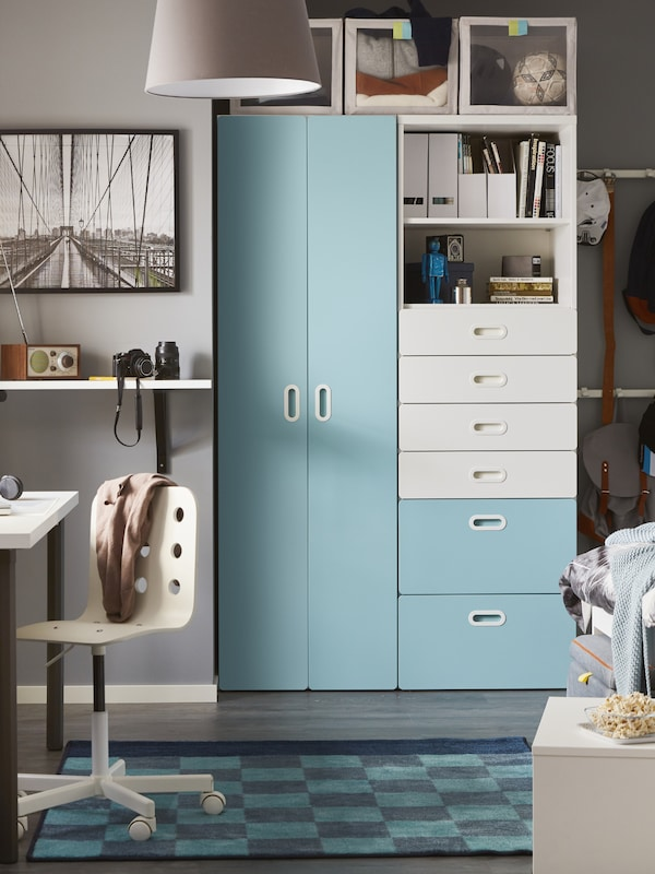 A child's room with a STUVA/FRITIDS wardrobe and drawer unit in light blue and white with a checked rug in front.