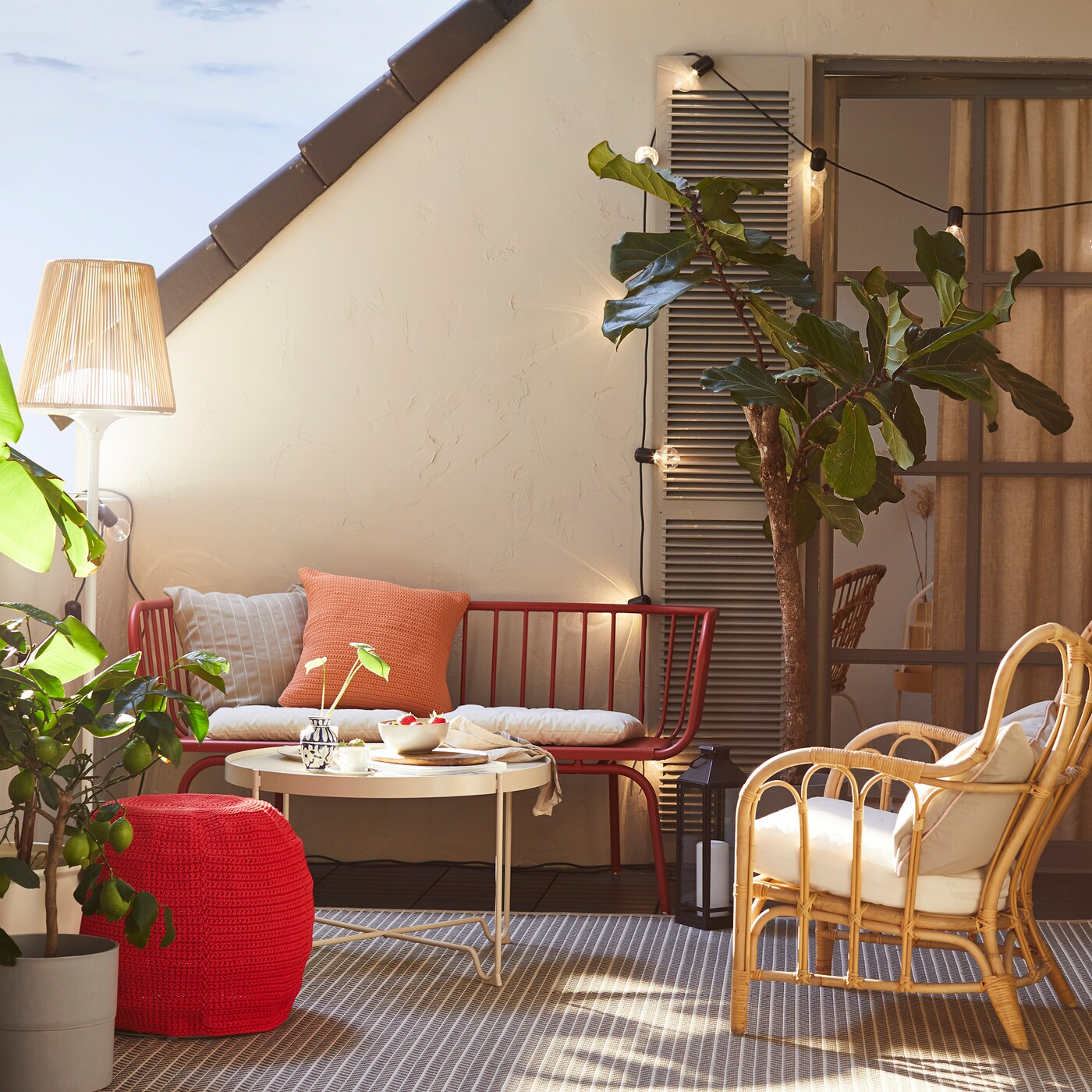 Outdoor balcony/patio, with BRUSSEN 3-seat outdoor sofa in red and a rattan chair with lots of greenery in plant pots.