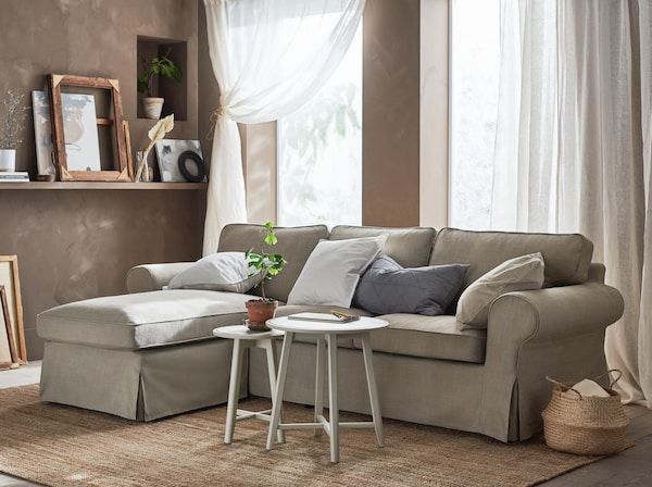 A beige sofa sectional with a chaise lounge in a living room with white curtains and tan walls