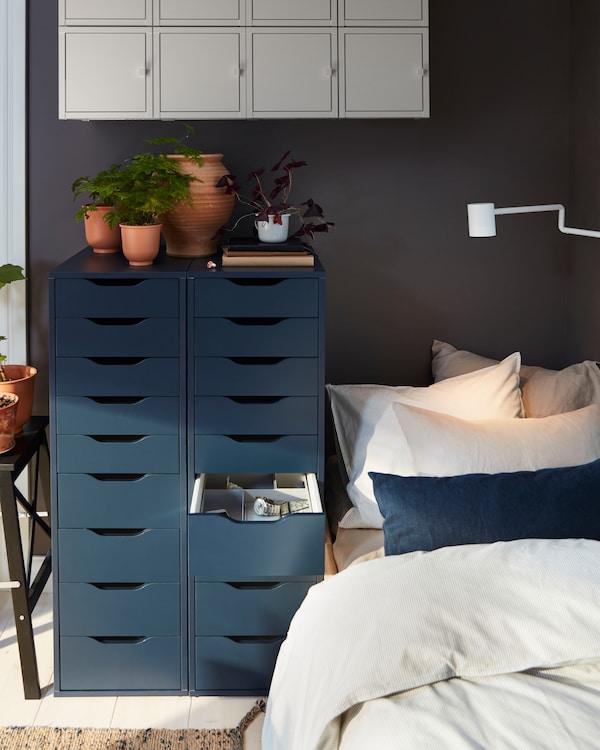 Säng med två höga mörkblå hurtsar intill, med terrakottafärgade krukor. Ovanför sitter väggmonterade skåp.
