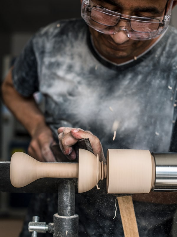 A wooden mushroom from the ANNANSTANS collection is being hand-turned by an artisan.